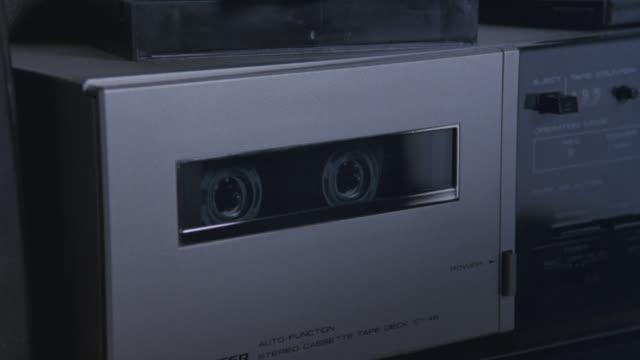 a tape recorder plays a cassette tape. - cassetta video stock e b–roll