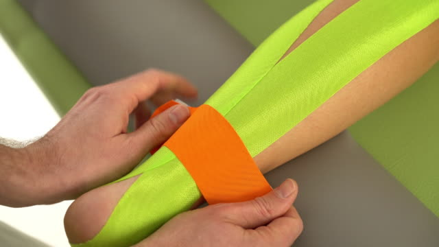 taping with elastic sports tape - bandage stock videos & royalty-free footage