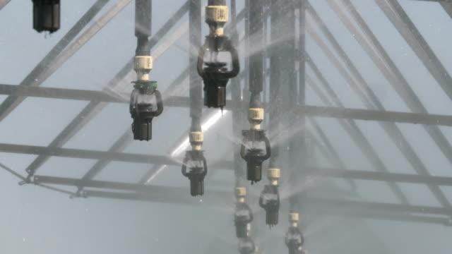 vídeos de stock e filmes b-roll de taps spraying water hanging from large centre pivot irrigation system - equipamento de irrigação