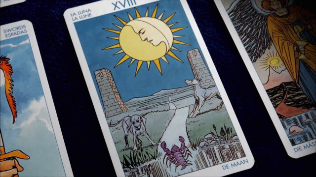 a tarot card displays the image of dogs alongside a sidewalk and a face in a sun. - tarot cards stock videos & royalty-free footage