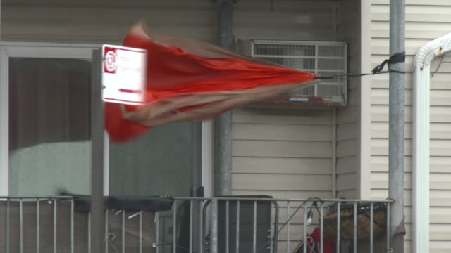 a tarp tied to a pole on the porch of a residential home and a parking sign blow violently in hurricane force wind gusts during tropical storm isaias... - scott mcpartland stock videos & royalty-free footage
