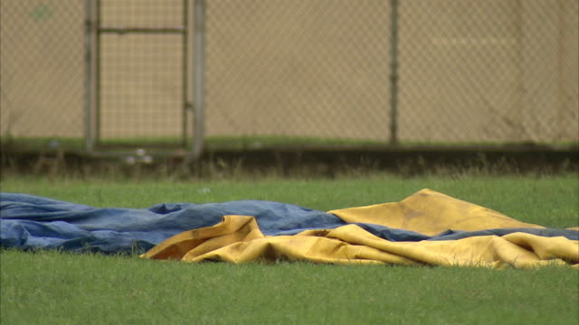 Tarpaulines lie on a cricket field. Available in HD.