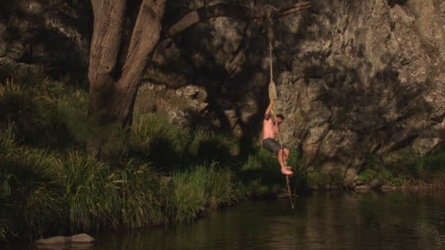 tarzan rope swing hanging on tree on side of stream pan to australian flag posted on a branch on a rock face and back / knot where rope is joined to... - rope swing stock videos & royalty-free footage