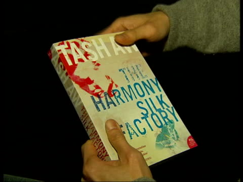 tash aw interview and british library gvs; tcms paperback copy of 'the harmony silk factory' held by tash aw/ cms tash aw's face - libro in brossura video stock e b–roll