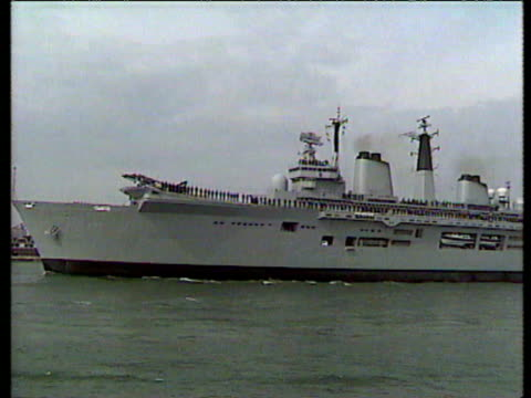 task force lead by hms invincible leaving for the falkland islands / crowds waving / banner on side of boat 'don't cry for me argentina' / people... - 1982 stock videos & royalty-free footage