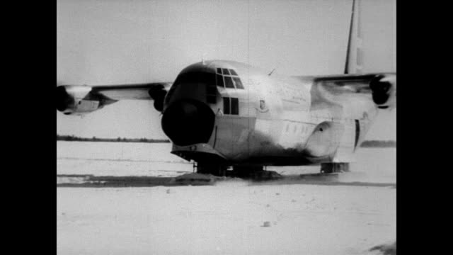 / task force slide members add skis to hercules cargo carrier / plane cruises around on the snow / plane takes off and skis retract / lands on skis.... - 1957 stock-videos und b-roll-filmmaterial