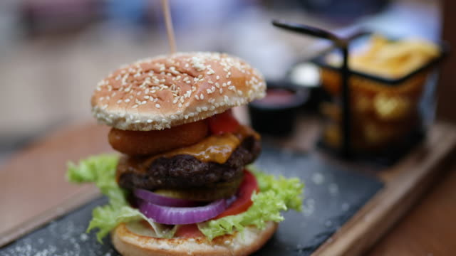 tasty cheeseburger served on appetizer plate at outdoor gastro pub - food and drink stock videos & royalty-free footage