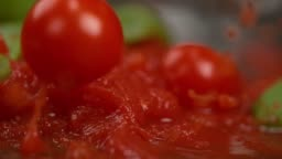 MACRO: Tasty tomato sauce with basil splashes as cherry tomatoes fall into it.