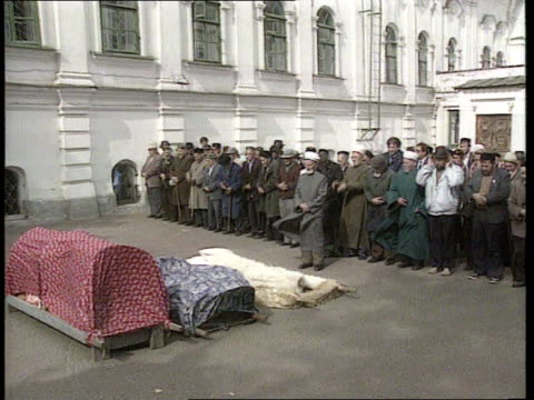 tatarstan to declare independence tatarstan seq muslim men kneel to pray sof gv mosque tilt down mourners at funeral as covered coffins on ground in... - 像点の映像素材/bロール