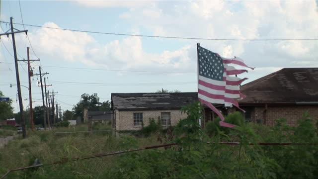 ms zo tattered american flag on fence blowing in wind in the ninth ward/ new orleans, louisiana - new orleans stock videos & royalty-free footage