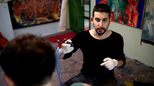 tattoo artist concentrates on his work - giuntura umana video stock e b–roll