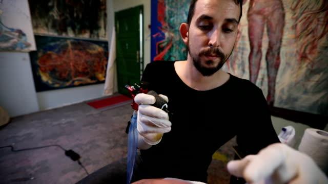 vídeos de stock e filmes b-roll de tattoo artist doing his job - membro humano