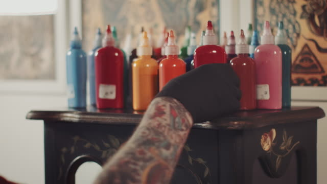 vídeos de stock e filmes b-roll de artista de tatuagem captar cor - tatuagem