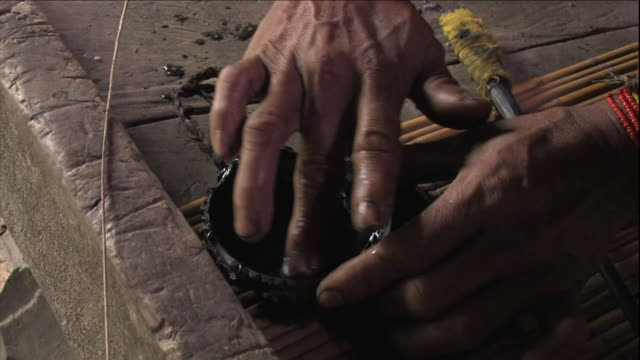 a tattoo artist in indonesia uses his fingers to mix dye in a small wooden bowl. - indigenous culture stock videos & royalty-free footage