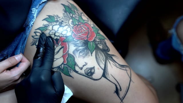 stockvideo's en b-roll-footage met tattoo kunstenaar maken tattoo op klant been - tatoeage