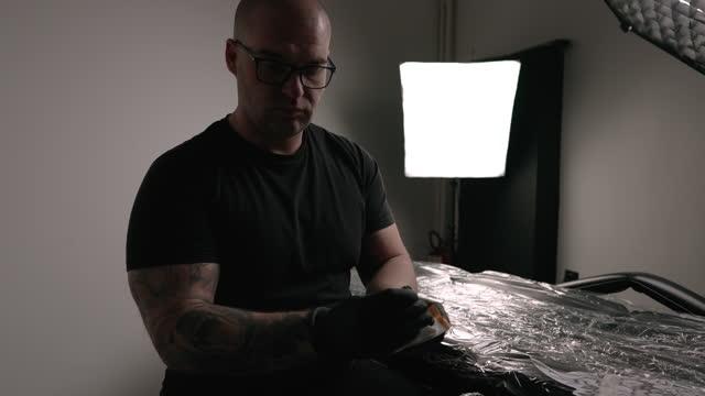 tattoo artist preparing his machine in the studio - black shirt stock videos & royalty-free footage