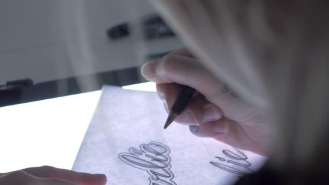 tattoo artist sketching handheld shot - artist stock videos & royalty-free footage