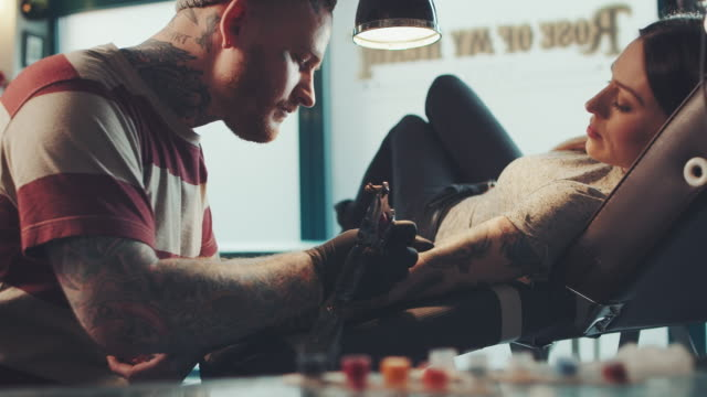 tattoo artist tattooing young woman - artist stock videos & royalty-free footage