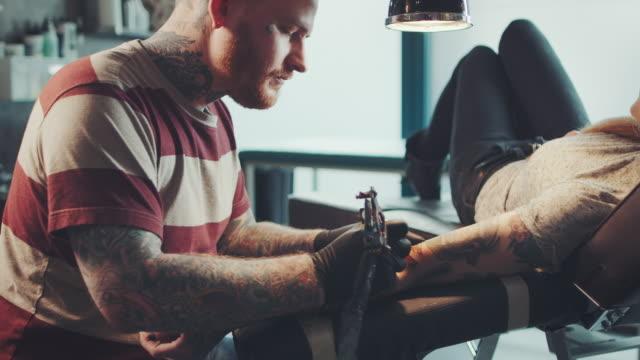 Tatoeëerder tatoeëren van jonge vrouw