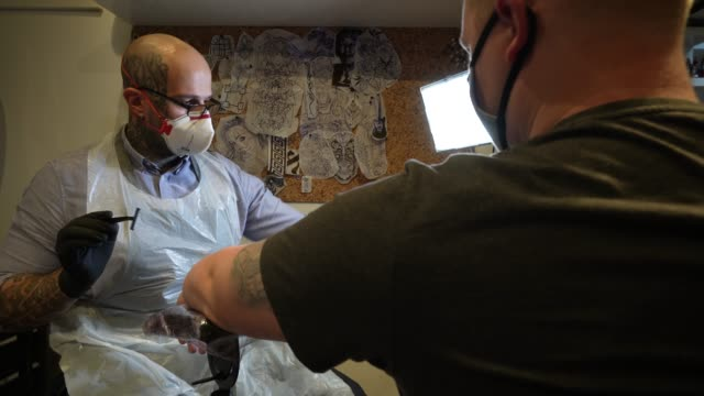 tattoo artist works on a clients tattoo whilst wearing a face shield as business return with covid-19 secure measures in place on july 22, 2020 in... - tattoo stock videos & royalty-free footage