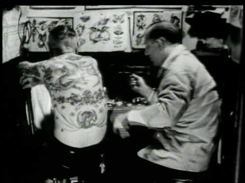 1946 MONTAGE tattoo artists working in shop / New York, New York, United States