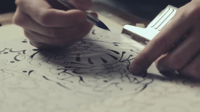 vídeos de stock e filmes b-roll de tattoo master drawing process - desenhar