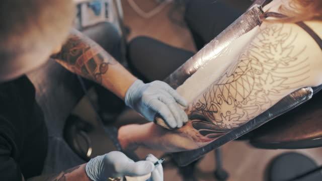 vidéos et rushes de maître de tatouage faisant un tatouage asiatique - tatouage