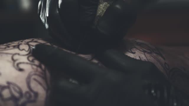 stockvideo's en b-roll-footage met tattoo meester maken van tatoeage op klant been - menselijke arm