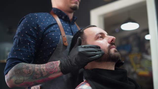 tattooed barber preparing customer for shaving - razor stock videos & royalty-free footage