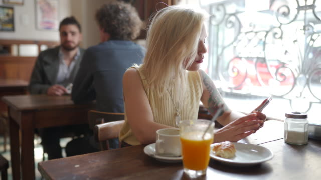 tattooed blond latina woman sitting in pub and using phone - nose ring stock videos & royalty-free footage