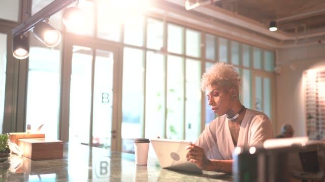 職場でデジタルタブレットを使用して入れ墨のビジネスウーマン - ピアスをあけた点の映像素材/bロール