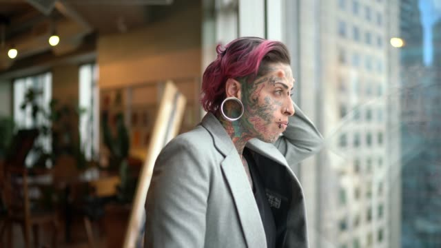 tattooed businesswoman worried looking through window at office - threats stock videos & royalty-free footage