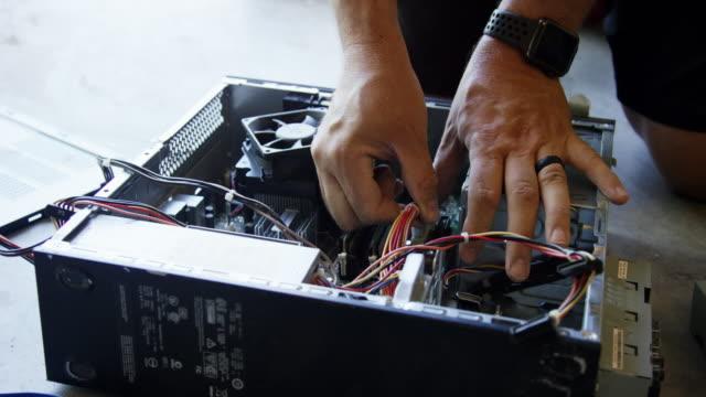 帽子をかぶった40代の入れ墨の白人男性は、床にひざまずいている間、コンピュータからマザーボードを取り除きます - 中央演算処理装置点の映像素材/bロール