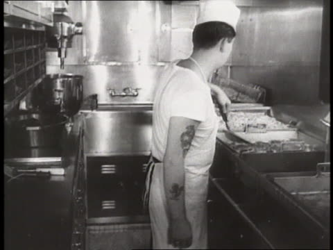 a tattooed cook flips steaks in the galley of the uss nautilus - galeere stock-videos und b-roll-filmmaterial