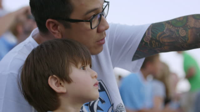 cu slo mo. tattooed dad explains game to son in crowded stadium bleachers at sporting event. - fan enthusiast stock videos & royalty-free footage