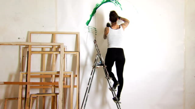 stockvideo's en b-roll-footage met tattooed female artist painting ws - schilderijen