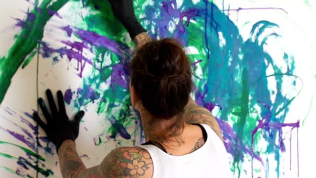 stockvideo's en b-roll-footage met tattooed female artist painting ms - canvas