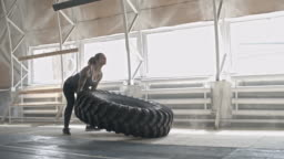 Tattooed Female Athlete Flipping Tractor Tire