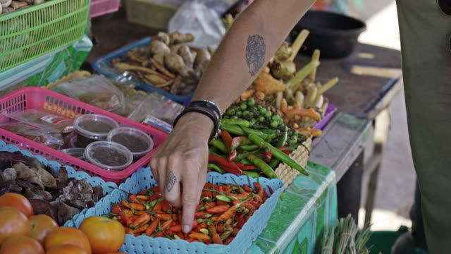 tattooed female hand picking up fresh chili peppers at fresh market thailand - exoticism stock videos & royalty-free footage