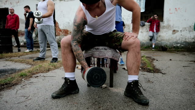 tattooed gang member exercising - cruel stock videos & royalty-free footage