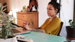 Tattooed Latina freelancer working from home or using E-Learning app