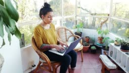 Tattooed Latina freelancer working from home