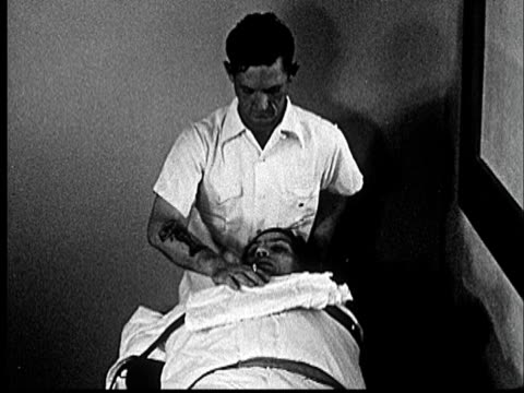 1953 MS Tattooed male nurse putting cushion under head of sedated man strapped onto stretcher/ Norman, Oklahoma