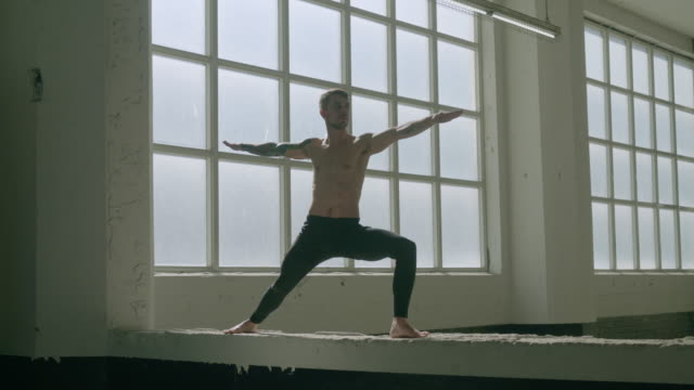 tattooed man doing yoga in industrial garage. - white caucasian stock videos & royalty-free footage