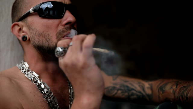 stockvideo's en b-roll-footage met tattooed man roken van een joint - gang