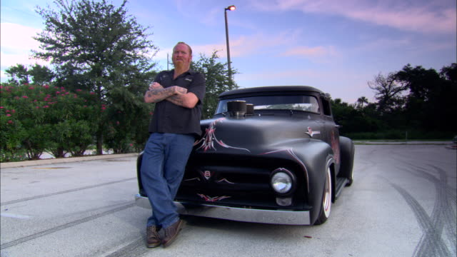ms, tattooed man standing by vintage car on road, jacksonville, florida, usa - sideways glance stock videos & royalty-free footage