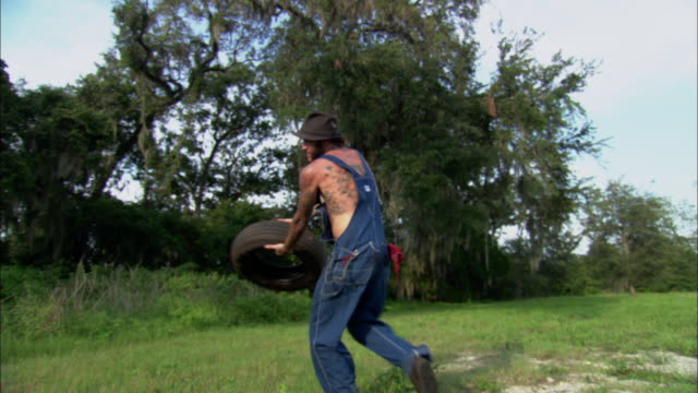 ms, cu, tattooed man throwing car tire, yelling towards camera, jacksonville, florida, usa - see other clips from this shoot 1403 stock videos and b-roll footage