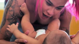 Tattooed mother playing with her cute baby on bed indoors.Mother's Day concept. Family, love, lifestyle, motherhood and tender moments concepts.Lifestyle: Home