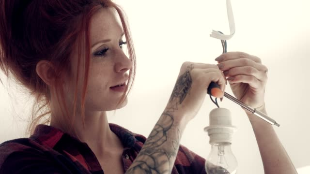 tattooed woman changing light bulb - tattoo stock videos & royalty-free footage