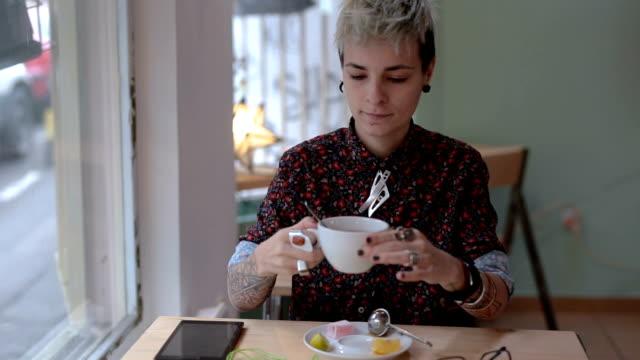 Tattooed woman drinking hot tea
